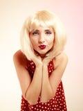 Utvikningsbrudflicka i retro klänning för blond peruk som blåser en kyss Royaltyfri Fotografi