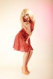Utvikningsbrudflicka i retro klänning för blond peruk som blåser en kyss Royaltyfri Bild
