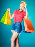 Utvikningsbrudflicka med shoppingpåsar som kallar på telefonen Royaltyfria Bilder