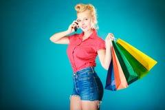 Utvikningsbrudflicka med shoppingpåsar som kallar på telefonen Arkivfoton