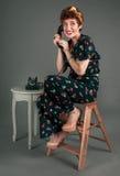 Utvikningsbrudflickan i blommig dräkt grinar medan på telefonen arkivbilder