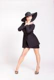 Utvikningsflicka med en stor svart hatt Arkivfoton