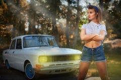 Utvikningsflicka nära den retro bilen på en bakgrund av skogen fotografering för bildbyråer
