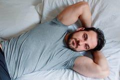 Utvilad färdig man som ligger i den bekväma sängkänslan fotografering för bildbyråer