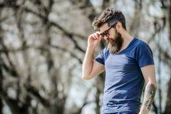 UV φίλτρο Γενειοφόρα προστατευτικά γυαλιά ηλίου ένδυσης ατόμων hipster βάναυσα Άτομο γενειοφόρο με το υπόβαθρο φύσης γυαλιών ηλίο στοκ φωτογραφία