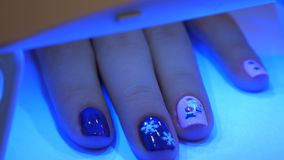 UV lamp gel polish manicure process in home conditions. New Year`s manicure. Hand in UV Lamp Nail Dryer. Woman Drying Nails. A manicure in the salon. Manicure in stock video footage