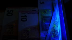 UV light using for checking euro banknotes. Counterfeit money detection. stock footage