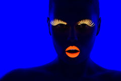 UV portrait. Close-up portrait of young woman wearing UV lashes and lipstick under blacklight Royalty Free Stock Photos