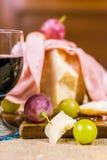 Uva amarela e vermelha ainda da vida - de muscat, queijo, salame e um vidro do vinho tinto em uma placa de madeira e em uma lona Imagens de Stock