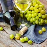Uva, botellas y vidrio de vino blanco con la uva en t de madera Imagen de archivo libre de regalías