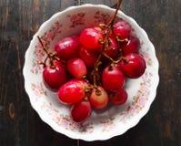 Uva cilena rossa in un piatto sopra una tavola di legno di marrone scuro immagine stock libera da diritti