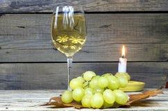 Uva con un bicchiere di vino e una candela Fotografie Stock