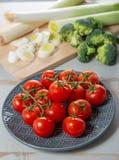 Uva de tomates de cereja no prato azul Fotografia de Stock Royalty Free