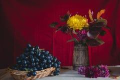 Uva di natura morta di autunno e fiori di autunno fotografie stock