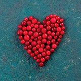 Uva-do-monte vermelha na forma do coração no fundo verde Foto de Stock Royalty Free
