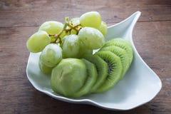 Uva e Kiwi Fruit verdi sul piatto bianco immagini stock