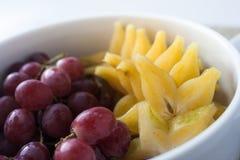 Uva e starfruit in una ciotola immagini stock