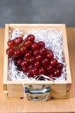 Uva en caja de madera en la tabla Imagen de archivo libre de regalías