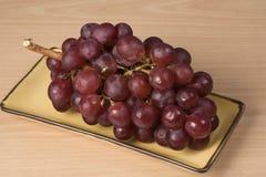 Uva en la tabla de madera, uva roja Imagenes de archivo