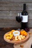 Uva, formaggio, fichi e miele con una bottiglia e un vetro della vittoria rossa Immagini Stock Libere da Diritti
