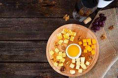 Uva, formaggio, fichi e miele con una bottiglia e un vetro della vittoria rossa Fotografie Stock