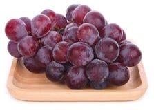 Uva fresca in ciotola di legno e su fondo bianco fotografia stock