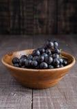 Uva fresca in ciotola di legno su fondo di legno Fotografia Stock