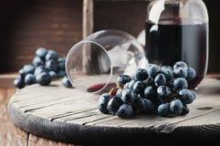 Uva fresca y vino rojo en la tabla del vintage Imagenes de archivo