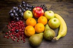 Uva matura, mele, banane, mandarini, pere, semi del melograno Fotografie Stock Libere da Diritti