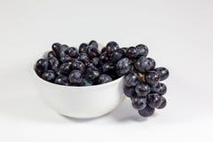 Uva nera in una ciotola bianca profonda su un racconto bianco che aspetta per essere mangiato fotografia stock
