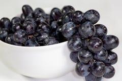 Uva nera in una ciotola bianca profonda su un racconto bianco che aspetta per essere mangiato fotografia stock libera da diritti