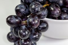 Uva nera in una ciotola bianca profonda su un racconto bianco che aspetta per essere mangiato fotografie stock