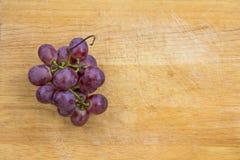 Uva púrpura en el fondo de madera de la textura Imagen de archivo