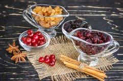 Uva passa in ciotola, mirtilli rossi, cannella ed anice sui tum di legno Fotografie Stock
