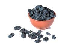 Uva passa nera in una tazza dell'argilla su un fondo bianco fotografia stock libera da diritti