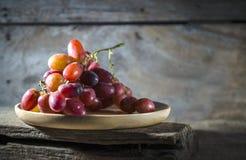 Uva in piatti di legno Fotografia Stock