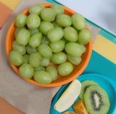 Uva in piatto ed arancia e mela arancio del kiwi accanto al piatto Fotografia Stock Libera da Diritti