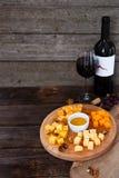 Uva, queijo, figos e mel com uma garrafa e um vidro da vitória vermelha Imagens de Stock Royalty Free