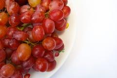 Uva roja en plato Imagenes de archivo