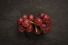 Uva rossa con le goccioline di acqua sull'ardesia Fotografia Stock