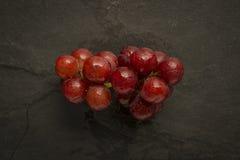 Uva rossa con le goccioline di acqua sull'ardesia Fotografie Stock Libere da Diritti