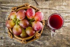 Uva rossa e succo del grepe sul bordo di legno Fotografie Stock