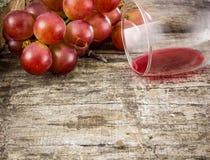 Uva rossa e vetro del succo del grepe sul bordo di legno Fotografia Stock Libera da Diritti