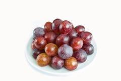 Uva rossa in un piatto bianco fotografia stock