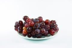 Uva rossa in un piatto bianco immagini stock libere da diritti
