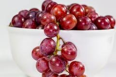 Uva senza semi rossa in una ciotola bianca profonda su un racconto bianco che aspetta per essere mangiato fotografia stock libera da diritti