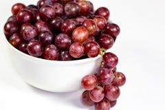Uva senza semi rossa in una ciotola bianca profonda su un racconto bianco che aspetta per essere mangiato fotografie stock libere da diritti