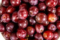 Uva senza semi rossa in una ciotola bianca profonda su un racconto bianco che aspetta per essere mangiato fotografie stock