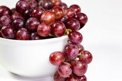 Uva senza semi rossa in una ciotola bianca profonda su un racconto bianco che aspetta per essere mangiato immagine stock