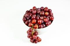 Uva senza semi rossa in una ciotola bianca profonda su un racconto bianco che aspetta per essere mangiato fotografia stock